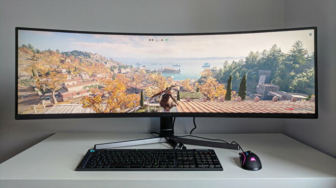 A photo of an ultrawide gaming monitor running Assassin's Creed Odyssey