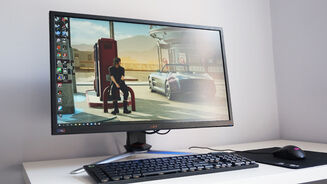 A photo of the Acer Nitro XV273K on a desk behind a mouse and keyboard