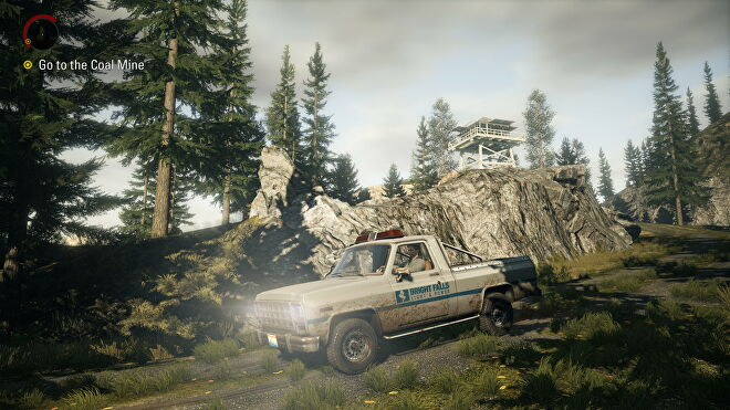 Alan Wake drives a truck through a forest in Alan Wake Remastered