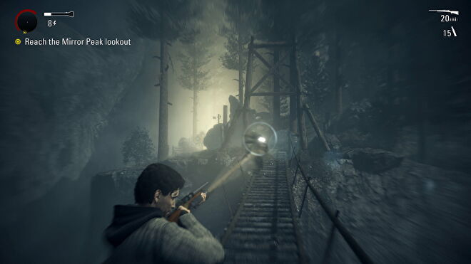 Alan aims a torch at a possessed man on a bridge from Alan Wake Remastered