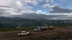A screenshot of American Truck Simulator's Wyoming DLC showing a truck driving on a road in front of a sprawling vista of river, mountains and trees.