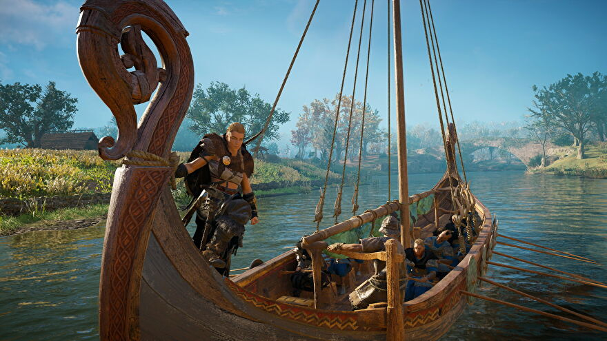 Assassin's Creed Valhalla - Eivor stands at the front of a boat while other vikings row and steer.