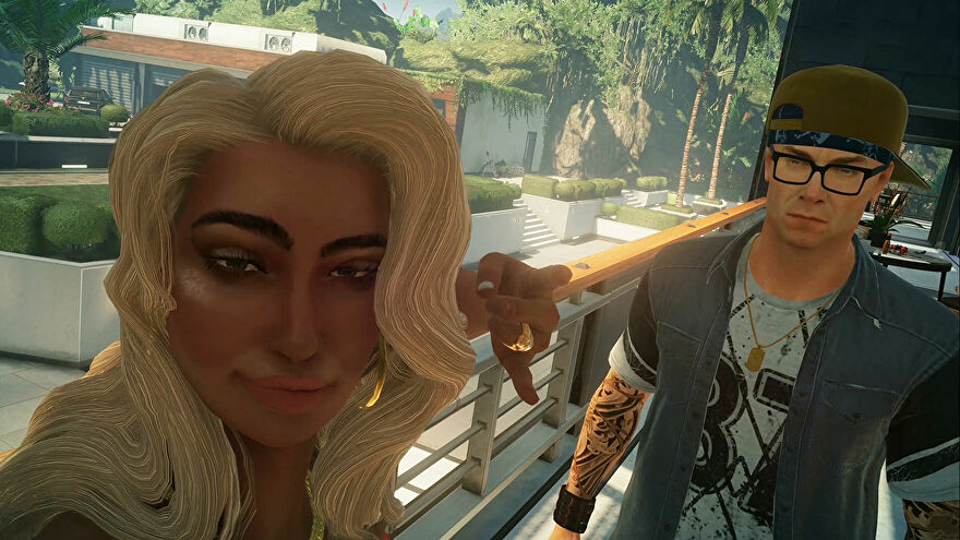 Agent 47, from Hitman, is disguised as a famous tattoo artist, with cap backwards and fake tattoos on his arms. He is in a selfie with a blonde woman throwing up the Shaka sign with her free hand