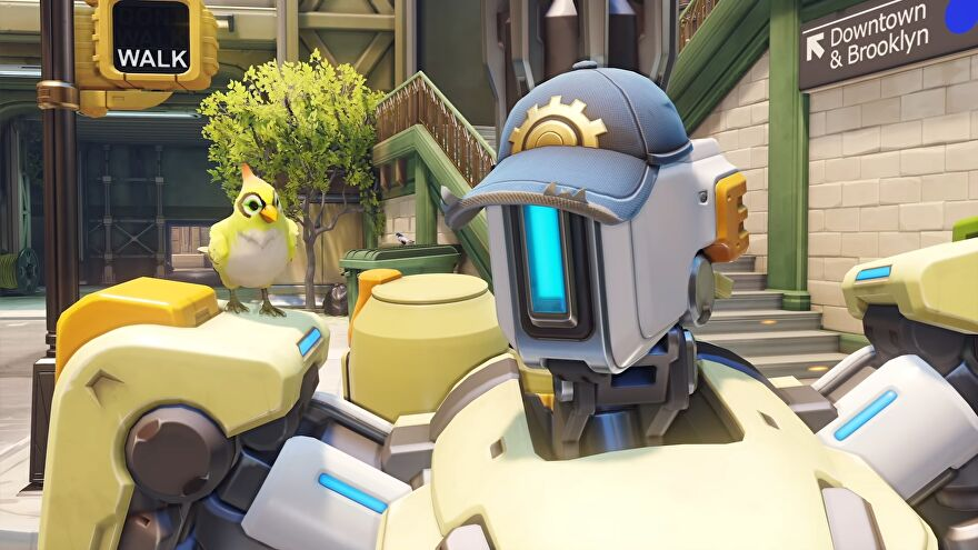 A close-up of Bastion in Overwatch 2, he's wearing one of Torbjorn's caps and Ganymede is sat on his shoulder.