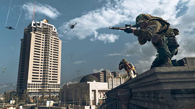 An image of Die Hard's Nakatomi Tower in Warzone, and just off to the side, a player aims down a sniper rifle, while another looks through some binoculars behind them.