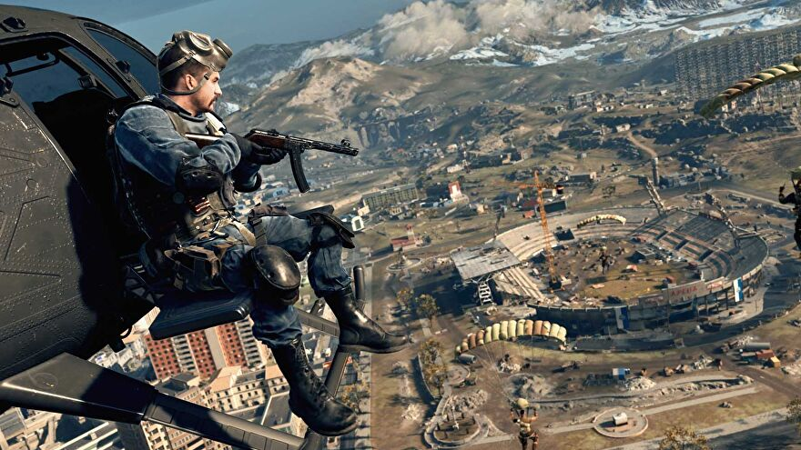 Call Of Duty: Warsone - A view from above the new Verdansk 1984 map. A player rides in a helicopter looking down at the stadium while others parachute in.