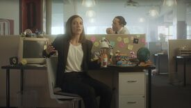 A still from Devolver Digital's E3 2021 showcase showing executive Nina Struthers sat on a chair in front of a desk while a man pinches food from her desk behind her.