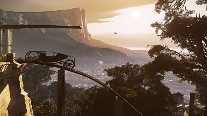 An image of Dishonored 2, which shows a view of Karnaca at sunset. A rail car is parked to the left and out in the distance the city rests below forests and cliffs.