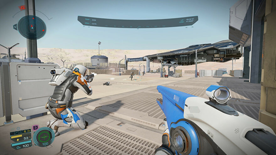 Elite Dangerous: Odyssey - One Commander in a space suit crouches, aiming a gun at a base on the surface of a dusty, beige planet. The first-person player holds a space-y looking blue and white rifle with a scope.