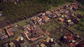 A screenshot of Endzone: A World Apart, showing from above some grass and trees and a lot of ramshackle houses built from repurposed wood and metal materials.