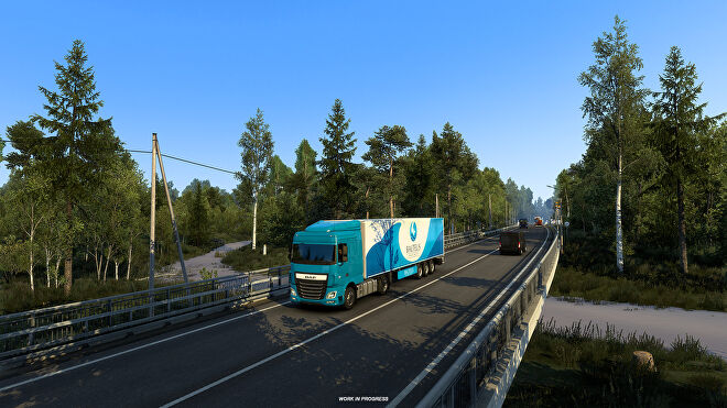 Euro Truck Sim 2 Russia- A truck drives down a two lane bridge through a forested area.