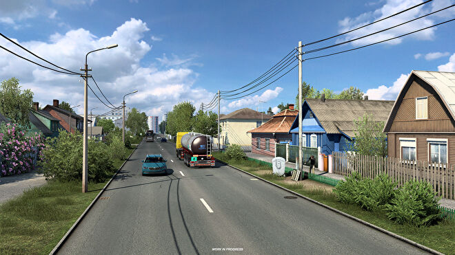 Euro Truck Sim 2 Russia - Trucks and cars drive on a two lane road between rows of colorful houses.