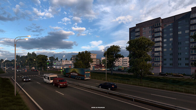 Euro Truck Sim 2 Russia - Cars and trucks on a four lane road drive past tall buildings and apartments at sunset.