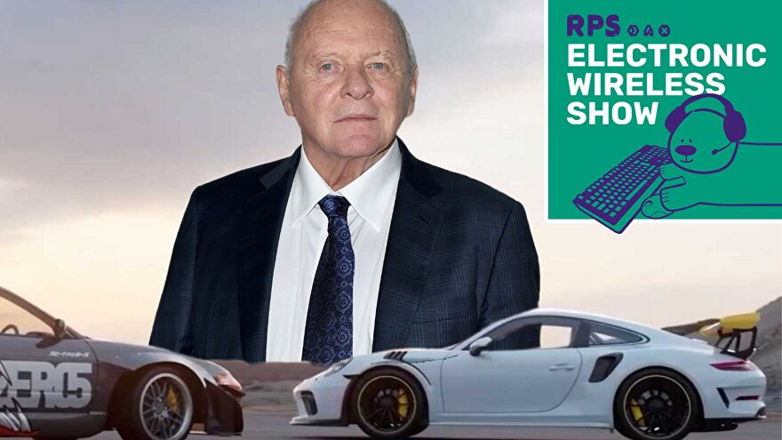 Sir Anthony Hopkins looks on as muscle cars drive in front of him