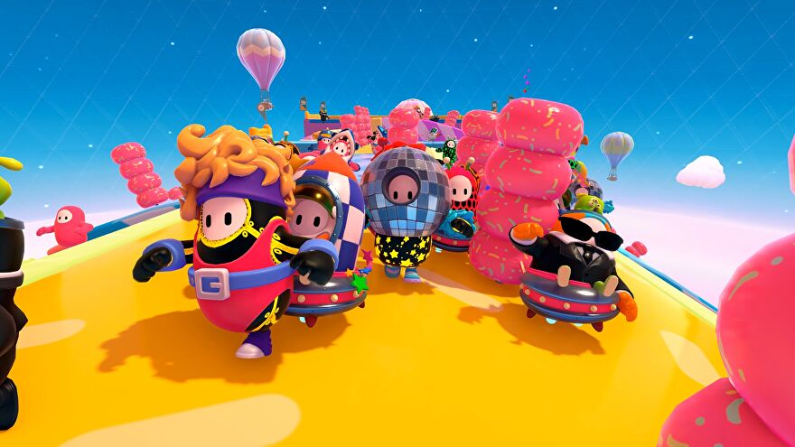 Several Fall Guys race along the new Roll On level, a large, rotating cylinder. They're all wearing new 80's inspired costumes such as a disco ball hat and a pink leotard with a belt and headband.
