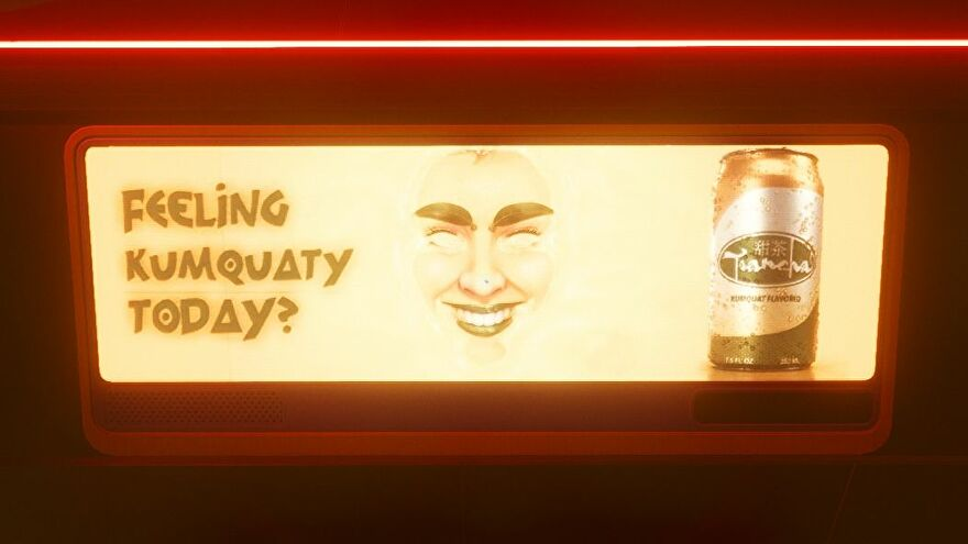 An advert from Cyberpunk 2077 for a kumquat flavoured drink. It is bright orange, with a creepy face in the middle next to the words 'FEELING KUMQUATY TODAY?'