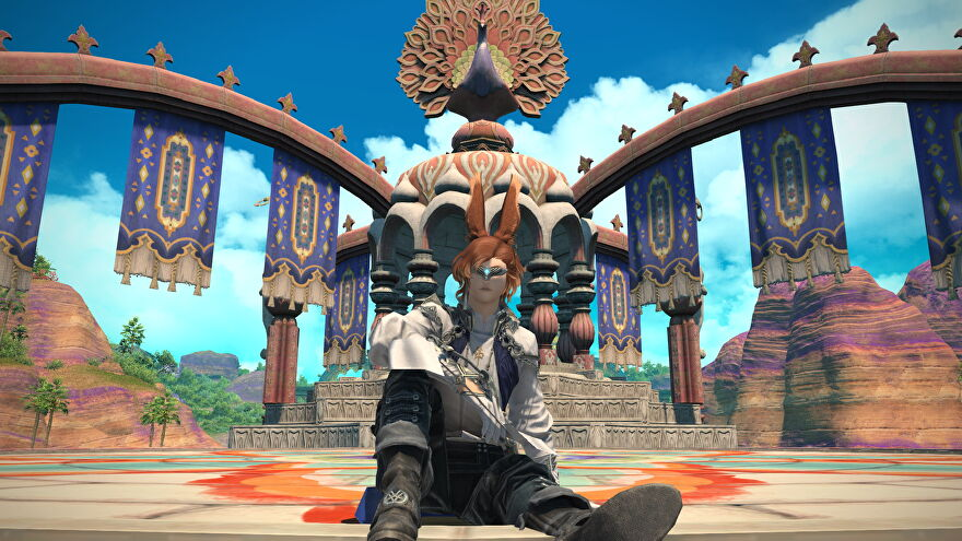 A male Viera sits back in front of a colourful peacock monument in Final Fantasy XIV: Endwalker.