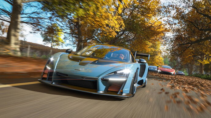 An image from Forza Horizon 4 which shows a blue supercar racing through a road surrounded by yellow autumn trees, and a cluster of other race cars lagging behind it.