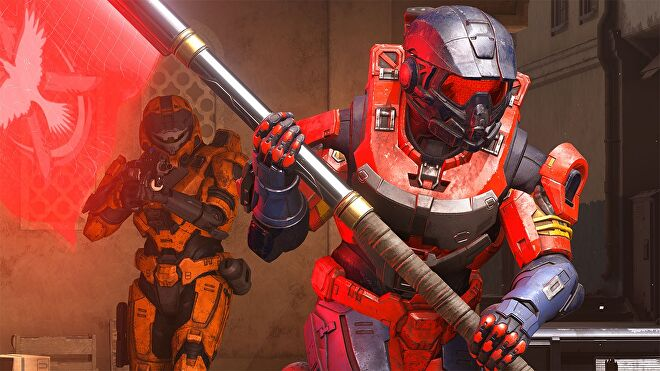 Halo Infinite - A player in red spartan armor is running and carries a red flag while a player in orange behind them holds a gun at the ready