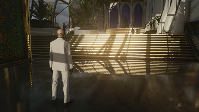 A screenshot of Agent 47 standing in front of a shiny set of stairs in Hitman 3's Dubai level