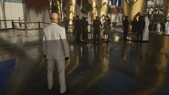 A screenshot of Agent 47 standing in a shiny reception hall from Hitman 3's Dubai level