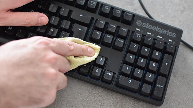 A keyboard being cleaned with a cloth.