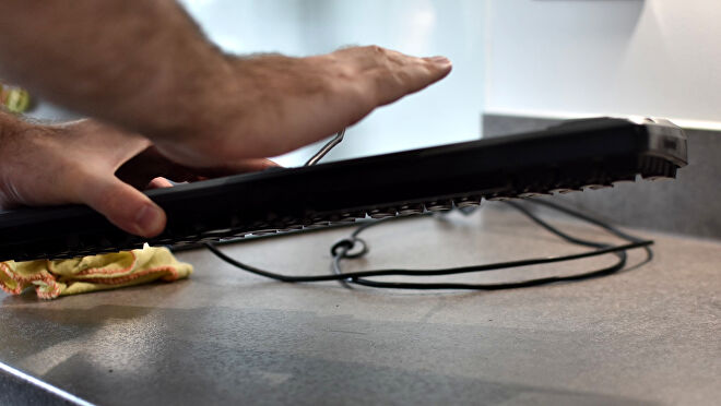 A keyboard being held upside down and shaken, so that dust and dirt falls out.