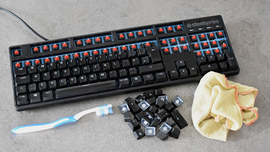 A keyboard, ready for cleaning, and various keyboard-cleaning items.