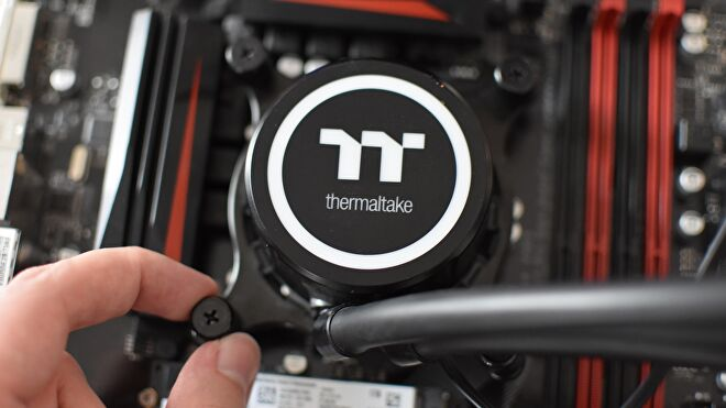 A hand tightens a thumbscrew on the mounting mechanism of a Thermaltake AIO watercooler.