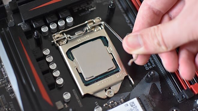 A hand pressing down on the locking arm of an Intel LGA 1151 motherboard socket, with an Intel CPU installed within.