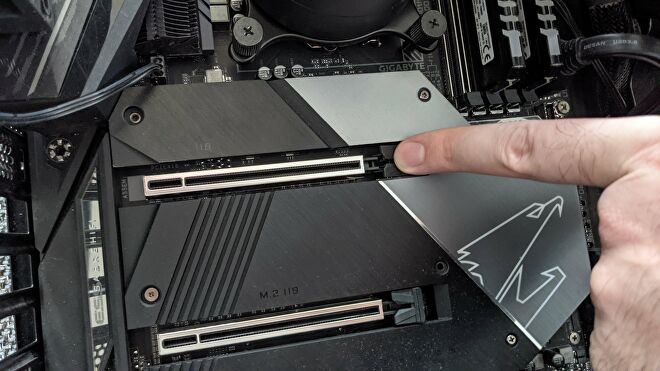 A finger presses down on the release latch of a motherboard's PCIe x16 slot.
