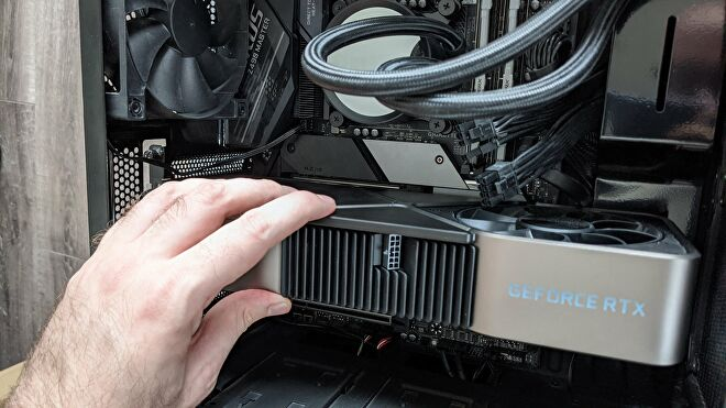 An Nvidia RTX 3090 graphics card being inserted into a motherboard's PCIe x16 slot.