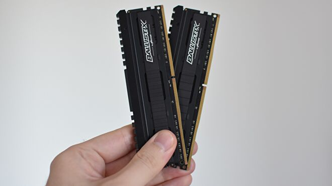 Two sticks of DDR4 RAM being held in a hand.
