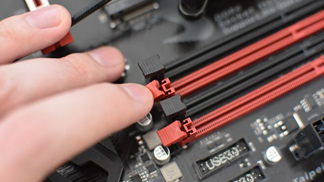 A hand opens the clasps on two motherboard RAM slots.