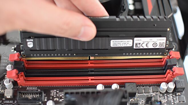 A stick of DDR4 RAM is lined up with its motherboard slot, shortly before it's pushed in.