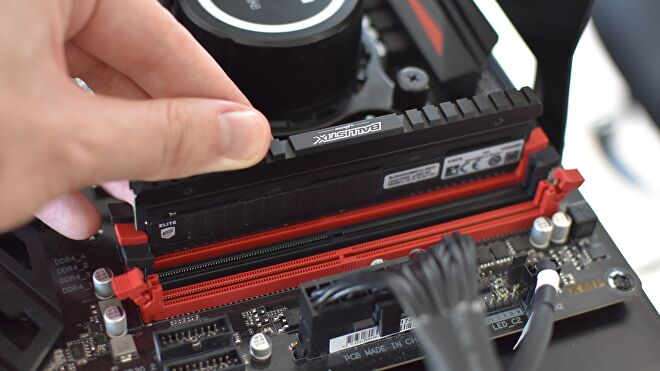 A stick of DDR4 RAM being pushed into its motherboard slot.
