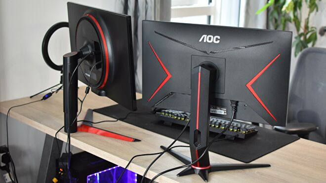 A rear view of two gaming monitors on a desk.