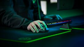 a photo of a gamer holding a razer viper ultimate mouse at a desk festooned with rgb lighting