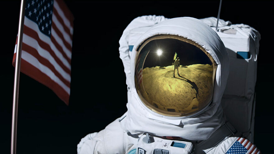 An astronaut on the Moon with a USA flag stares at another astronaut holding a Brazillian flag.