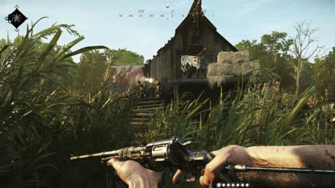 A player holds a revolver and lurks behind tall grass in Hunt: Showdown.