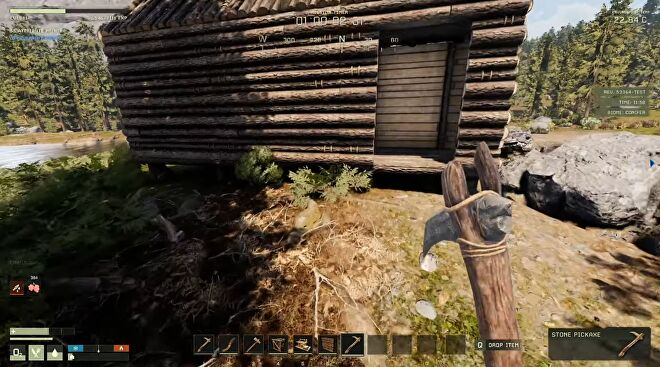 Icarus - In first person, the player holds a handmade stone axe while looking at a log cabin surrounded by woods.