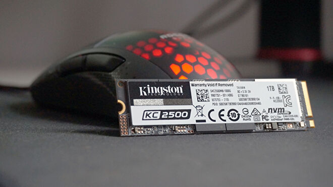 A photo of the Kingston KC2500 SSD in front of an RGB gaming mouse
