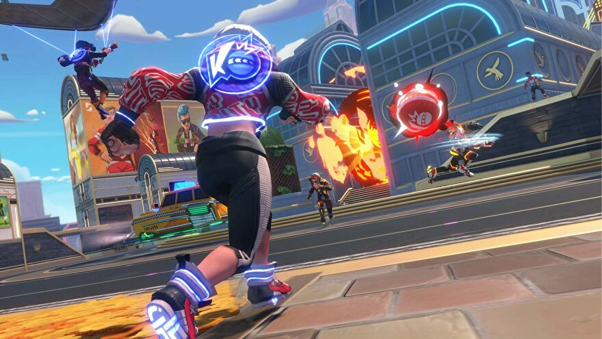 Knockout City - A player wearing athletic clothes and sneakers with glowing soles throws a red dodgeball at another player in a city courtyard with other players nearby.