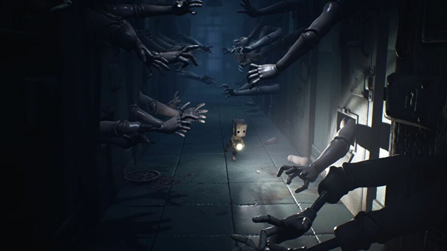 Mono from Little Nightmares II, a small boy with a brown paper bag on his head, runs down a corridor holding a torch. Tens of wooden dummy hands are reaching for him from behind locked metal doors