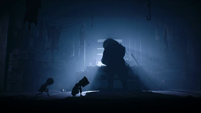 A screenshot from Little Nightmares II showing Six and Mono creeping behind the silhouette of a large man, who is skinning animals at a table in front of a boarded up window