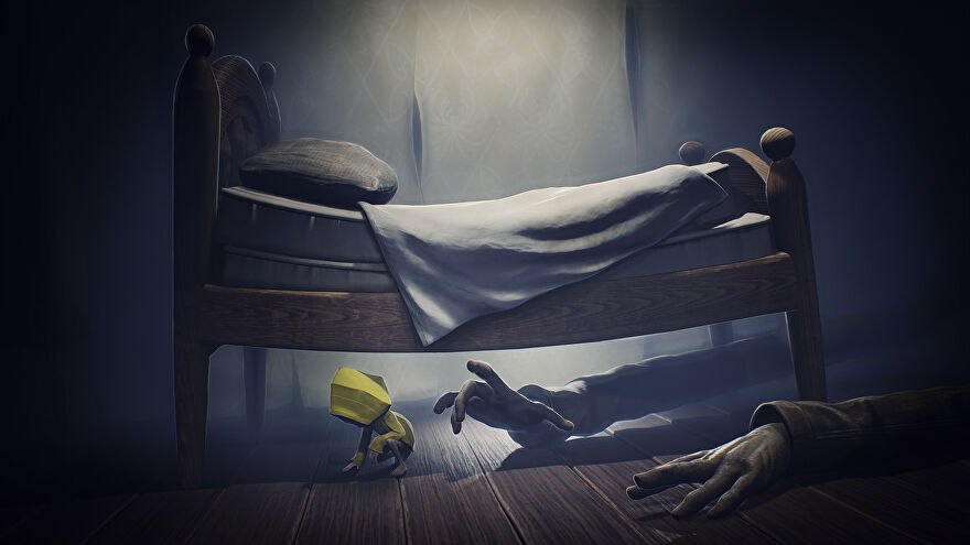 A screenshot of Little Nightmares showing a person in a yellow mac hiding under a giant bed while creepy long arms reach under to get them.