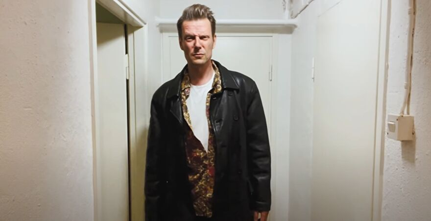 A still of a video showing Sam Lake in his Max Payne clothes.