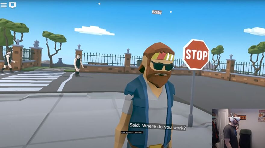 "An image showing an NPC from the VR game creation sandbox Modbox. In the corner is a developer wearing VR goggles. Text at the bottom of the screen reads, ""Said: Where do you work?"""
