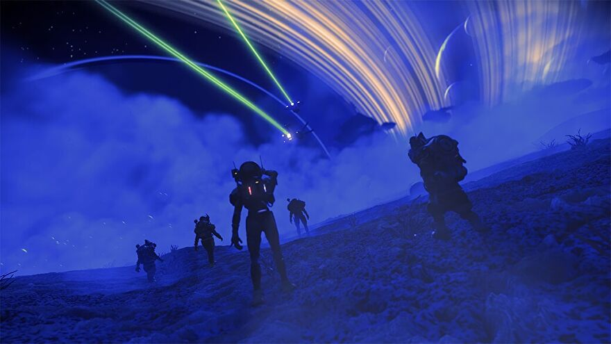 No Man's Sky - Several players walk across the surface of a desert planet at night, looking up at two starships flying past the planet's rings above.