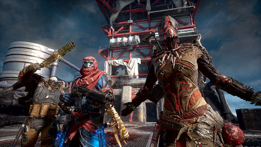 """A screenshot from Outriders, which shows three players facing the camera. One raises their weapon, one stands there looking cool, and the other strikes a """"You want some?"""" pose."""